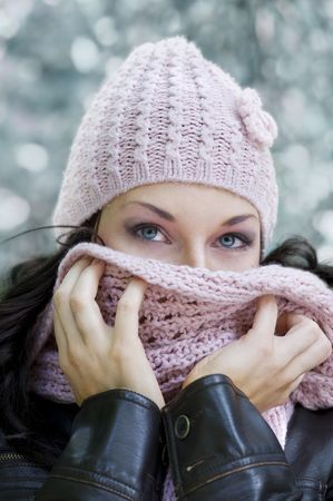 close up of a girl in a winter day covering her face from the cold wind photo