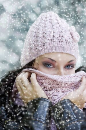 cute girl with stunning eyes covering her face from a cold winter with pink scarf  photo