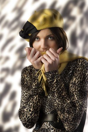 studio shot of very cute girl in winter spotted dress covering face with scarf photo