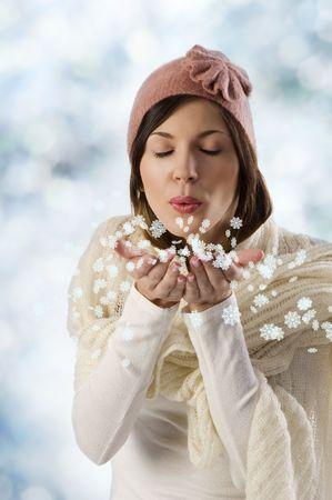 pretty sweet girl blowing de copos de nieve con bufanda blanca y un gorro de invierno color de rosa en un tiro de estudio de Foto de archivo - 5679957