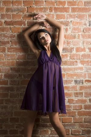 cute and sensual asian girl wearing purple nightgown posing against a brick wall  Stock Photo - 5693613