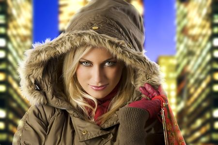 close up portrait of blond young woman in winter jacket covering head with hood photo