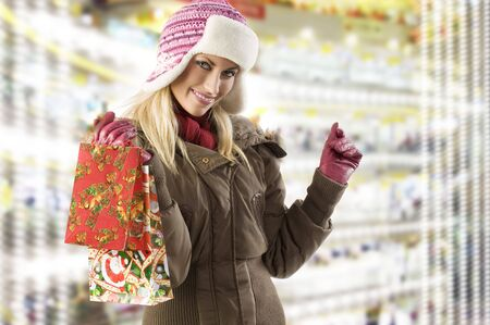 very cute blond girl in winter dress with hat and gloves and shopping christmas bag photo