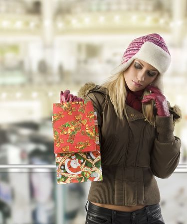 pretty blond girl in winter dress with hat and gloves looking at her shopping christmas bag