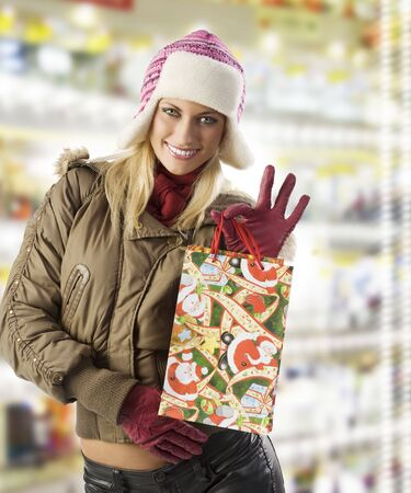 beautiful blond girl in winter dress with hat and gloves showing her shopping christmas bag photo