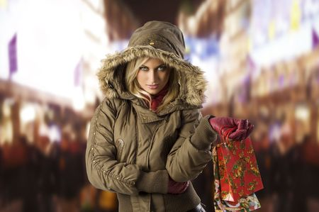 fur hood: attractive blond woman with shopping bag covering her head with hood from winter Stock Photo