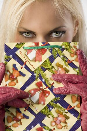 close up on the eyes of a young woman hiding face behind a shopping christmas bag photo