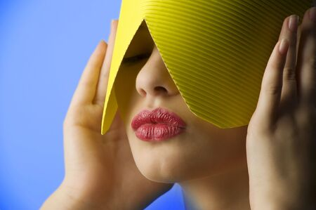 beauty portrait of a young woman with a yellow paper mask and red lips on blue background photo