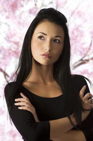 studio shot of graceful asian girl in black dress with dark hair photo