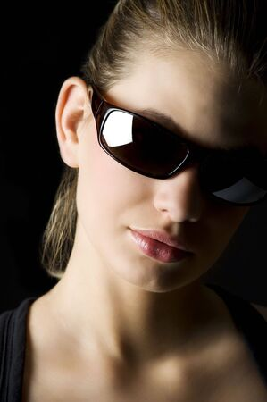 strong light studio shot of beautiful blond woman with black sunglasses  photo