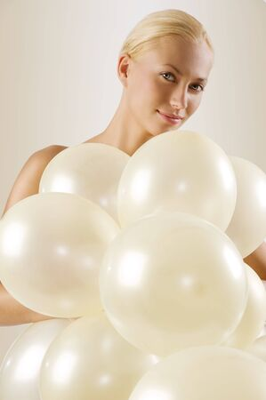 beautiful blond woman playing  with white balloons and looking in camera smiling photo