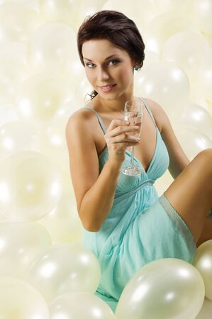 pretty and young brunette with a glass of champagne sitting between balloons photo
