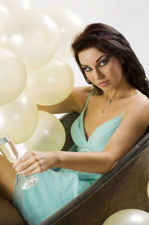 very cute girl in old bath with glass of champagne and strong fashion make up and balloons photo