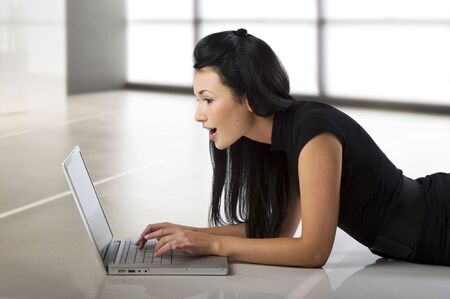 beautiful young oriental woman looking at the laptop with a surprised expression photo