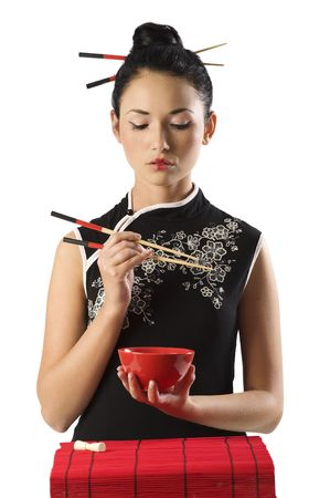 chinese symbol: beautiful asian girl in japanes dress eating oriental food from a red cup using chopstick