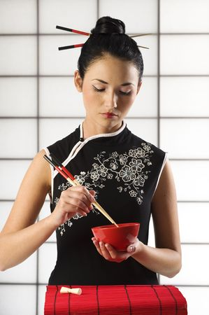 beautiful asian girl in calssic oriental dress in act to eat with chopstick photo