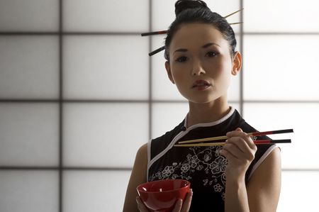japanes: nice back light shot of a beautiful asian girl in japanes dress eating and using chopstick  Stock Photo