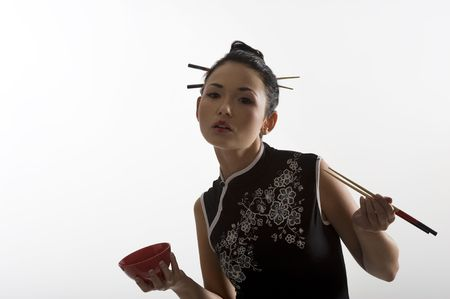 japanes: beautiful asian girl in japanes dress eating oriental food from a red cup using chopstick