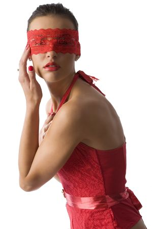 cute and sexy brunette in red shirt and a red lace mask with a hand near face 
