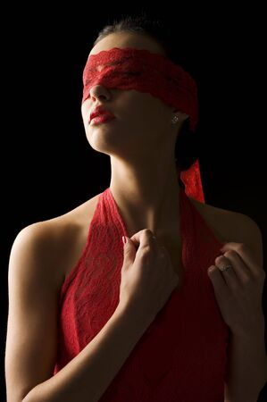 sensual portrait of a young brunette on black background with a red mask of lace Stock Photo - 6273904