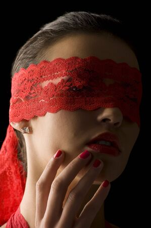 close up portrait of a young brunette on black background with a red mask of lace Stock Photo - 6273903