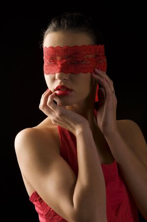 sensual portrait of a young brunette on black background with a red mask of lace Stock Photo - 6273906