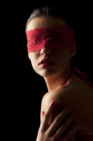 red head girl: sensual portrait of a young brunette on black background with a red mask of lace Stock Photo