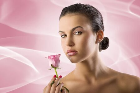 close up portrait of a pretty brunette with a pink rose looking in camera photo
