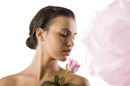 scents: close up portrait of a cute girl brunette looking a pink rose  Stock Photo