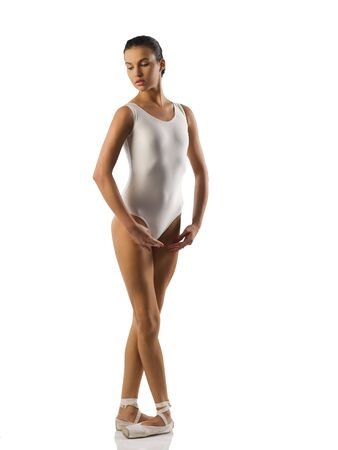 Young caucasian brunette ballerina girl performing a dance on white background and white floor photo
