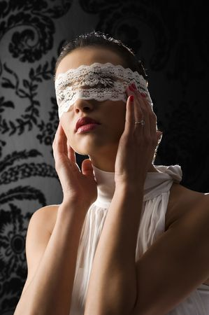 pretty young woman with dark hair wearing a white shirt and a white lace mask on black background photo