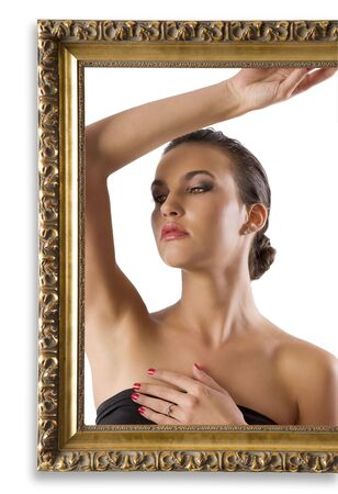 portrait of young and graceful brunette posing behind an old fashion picture frame photo