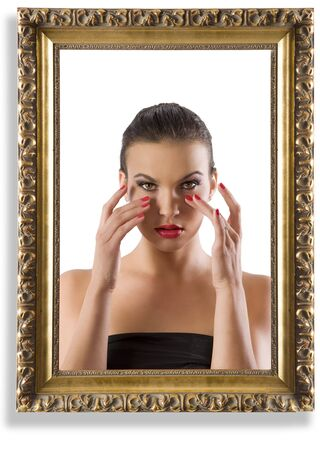 fashion portrait of beautiful woman looking at her make up inside an old frame photo