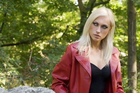 Closeup portrait of a sensual blond girl with red coat outside in a park photo