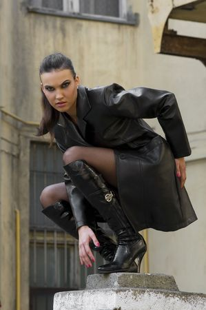 sexy girl vampire with black leather coat outside during night on the top of pilaster building photo