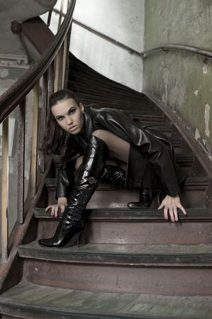 fashion shot of a brunette model with black leather coat and boots posing in old stairs photo