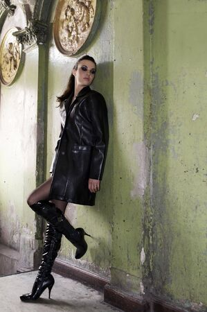 dark model wearing a leather coat and boots in an old fashion main entrance of old house Stock Photo - 6435109