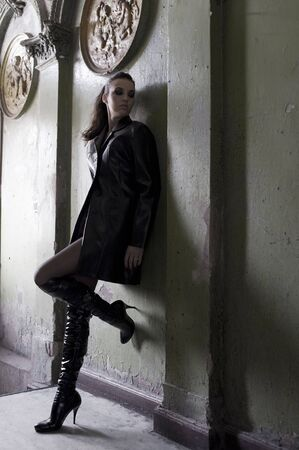 dark model wearing a leather coat and boots in an old fashion main entrance of old house photo