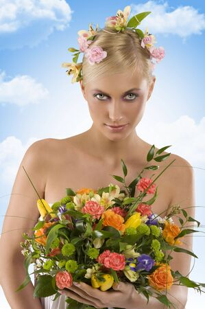 arm bouquet: young blond woman with flower on head and keeping a colored bouquet in her arm Stock Photo