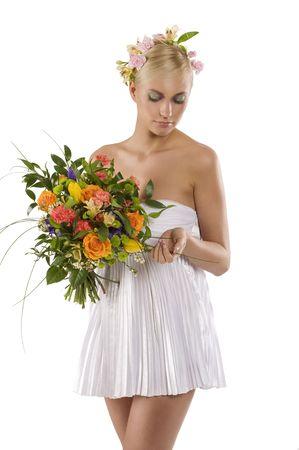 young and beautiful woman in short white dress with flower in hair and keeping a color bouquet  photo