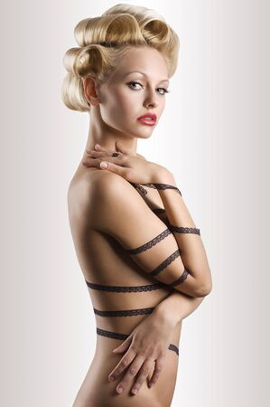 attractive blond girl with a fashion hair stylish and a strip lace around her naked body photo