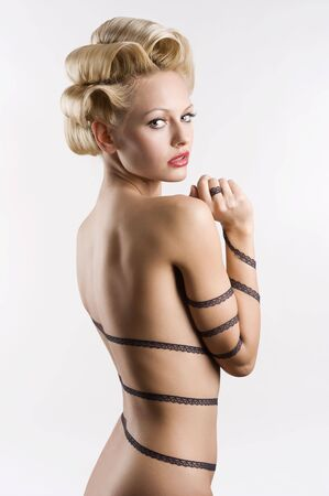 nude art model: attractive blond girl with a fashion hair stylish and a strip lace around her naked body looking in camera