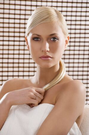 beauty advertising shot of a blond girl with a wood curtain behind like in a spa photo