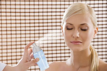 beauty advertising shot of a blond girl in act to be in a wellness farm with towel and cosmetic product photo