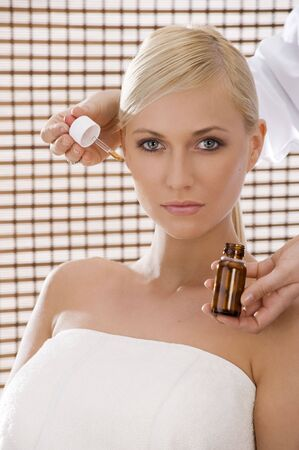 beauty advertising shot of a blond girl in act to get some\ cosmetic product for the skin