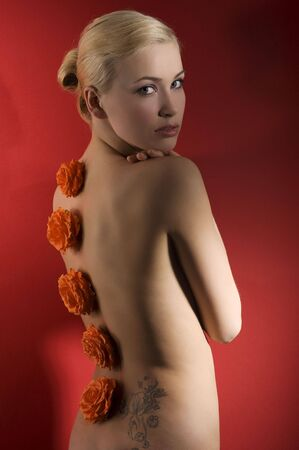 cute blond girl on red background with some flowers on her back like an ornament looking in camera photo