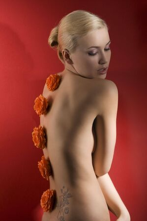 cute blond girl on red background with some flowers on her back like an ornament photo