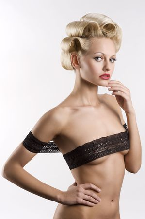 very sexy and beautiful blond woman with a pretty fashion hair style wearing a black lace as a bra around her nude body photo