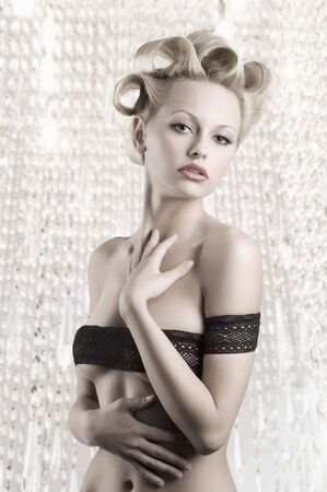 very sexy and beautiful blond woman with a pretty fashion hair style wearing a black lace as a braaround her naked body photo