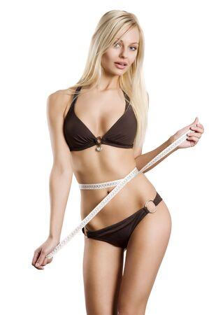 girls underwear: young blond woman measuring her body with a tape and looking in camera . healthy lifestyles concept
